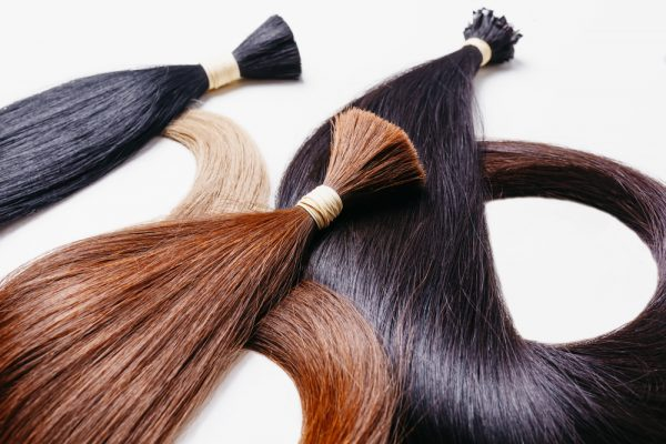 Hair extensions of different colors lay flat on a table. Instead of cutting your hair try adding some instant length to it!