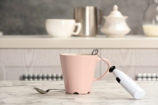 Handheld frother laying on a pink mug on a marble table top in an all white kitchen.