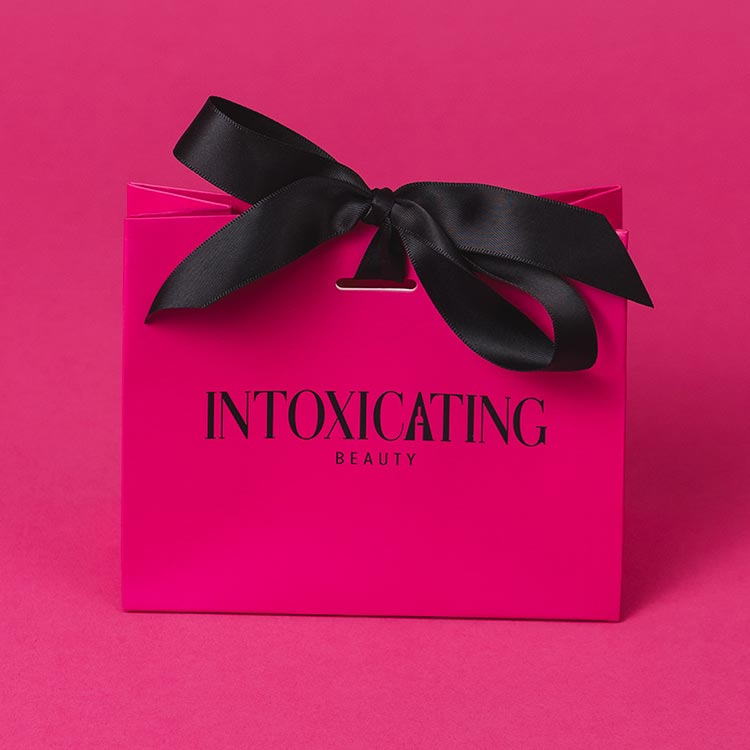 Intoxicating Beauty pink gift bag with black bow.