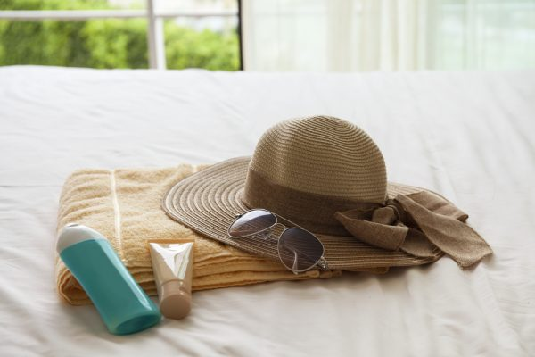Multiple lotions sit next to a hat, towel, and sunglasses on a bed. Read on to learn about the difference between chemical and physical spf lotions.