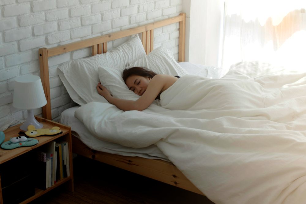 Woman in bed resting on her side - learn ways to get better beauty sleep during quarantine.