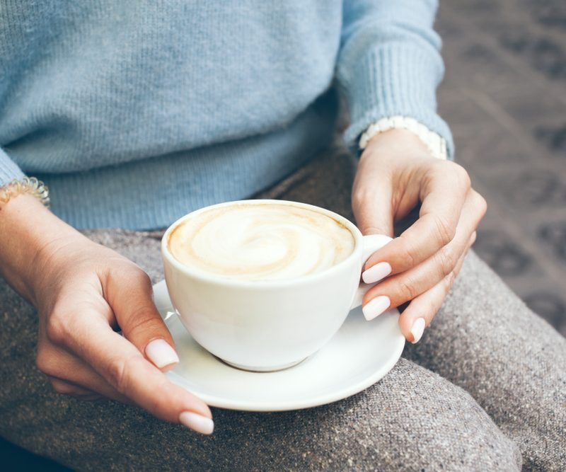 Woman in blue sweater holding a cup of coffee - add adaptogens to your morning joe for a change in flavor..