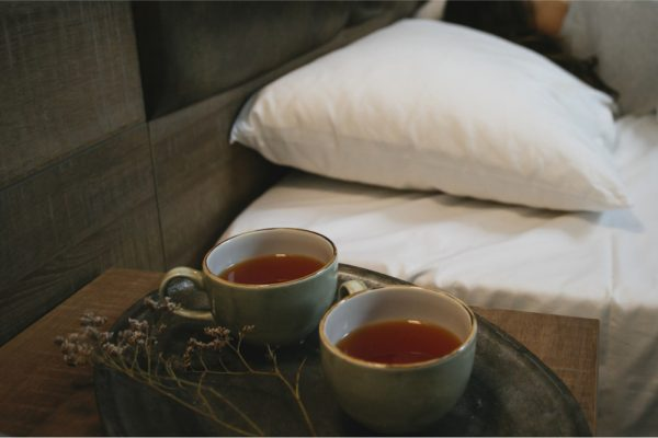 Woman sleeps in the bed next to two cups of tea - drinking warm tea before bed can signal your body to sleep.