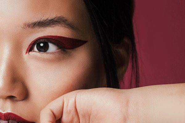 Woman with red graphic eyeliner applied.