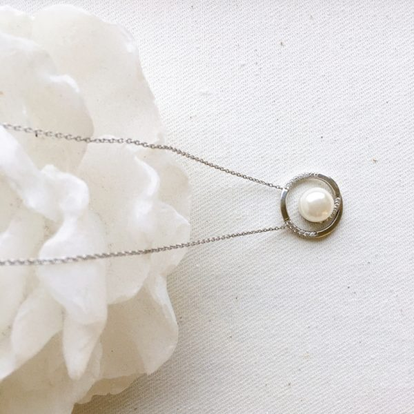 Single pearl necklace on a white flower bud - some mother's may love jewelry as a gift for Mother's day.