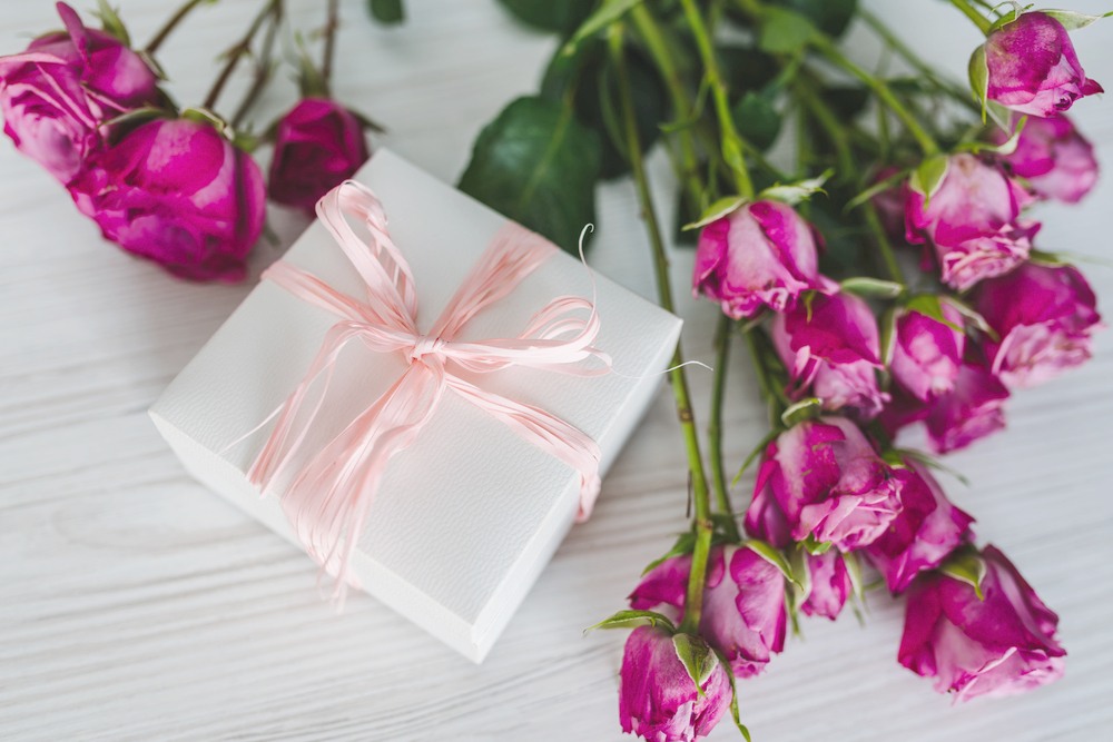 Gift box with pink ribbon next to pink flowers - read along to learn about our recommendations for mother's day gifts.