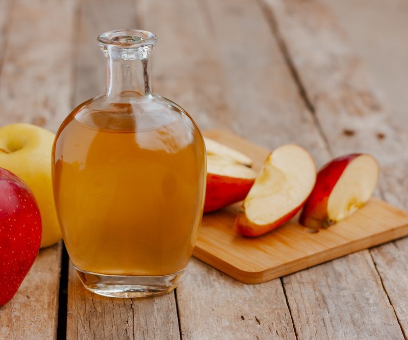 Apple cider vinegar in a jar, apples, and sliced apples on a cutting board on top of a wooden table.