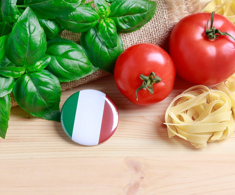 Italian flag on a pin on button, tomatoes, green leaves, and pasta.