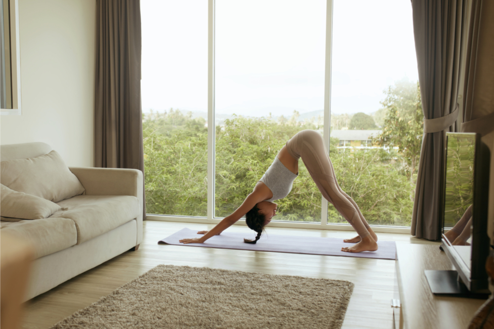 Woman in a yoga pose at the comfort of her home.