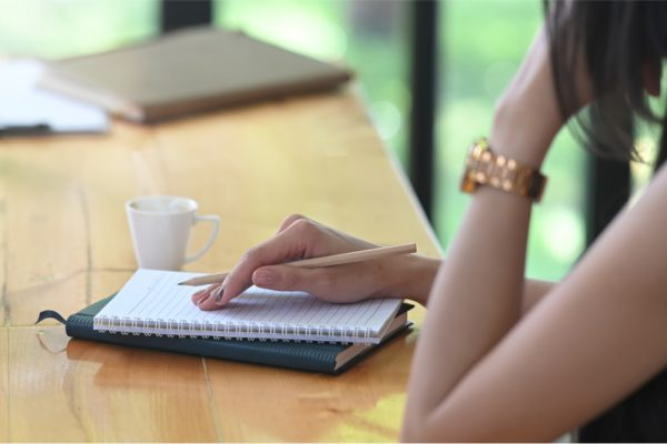 Woman thinking as she prepares to write into a planner.