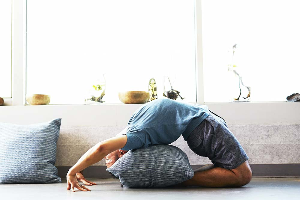 Man stretching his back backwards over a pillow.