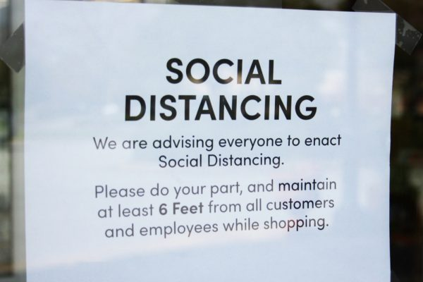 Social Distancing sign posted on door, maintain at least 6 feet from all customers.
