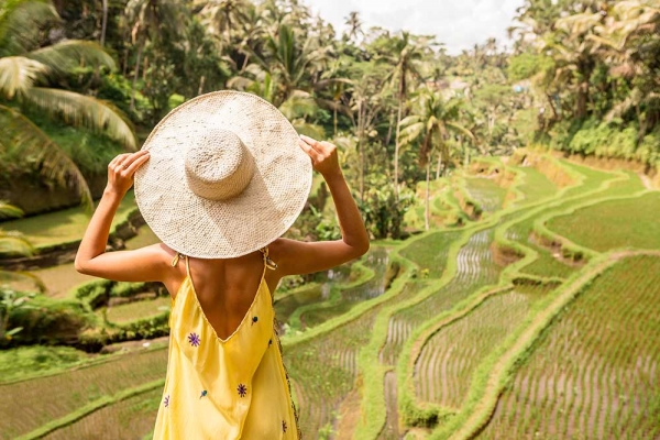 Woman looking at a rice field while holding onto her hat