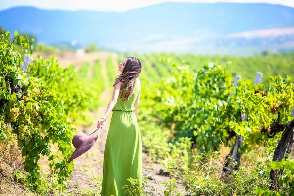 Woman running through a vineyard wearing a green dress.