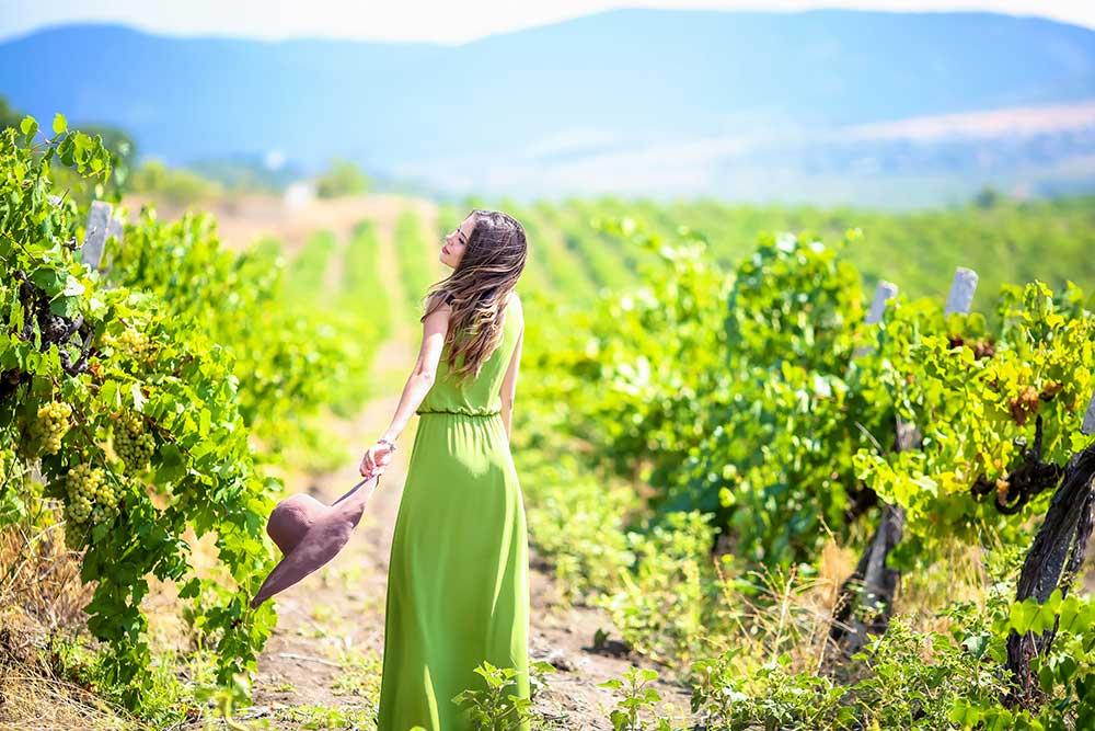 Woman running through a vineyard wearing a green dress.