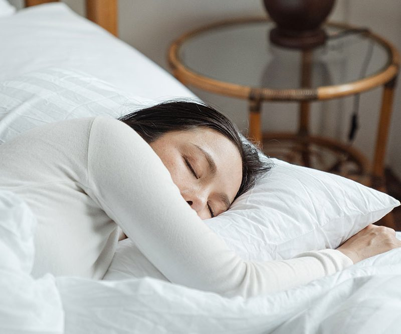 Woman sleeping in a bed during daylight
