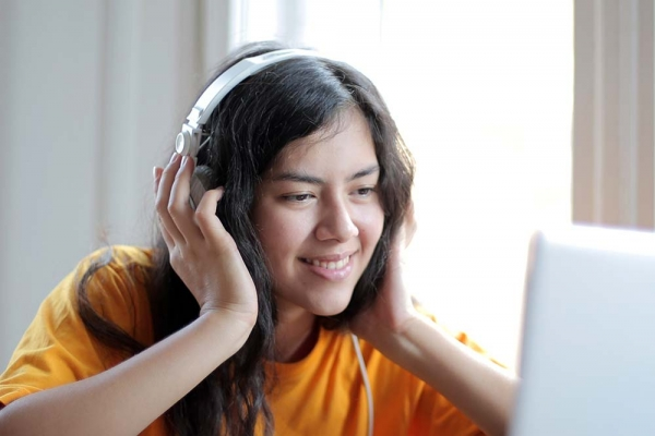 Listening to music with headphones on while tending to laptop.