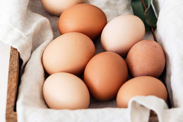 White and brown eggs in a basket.