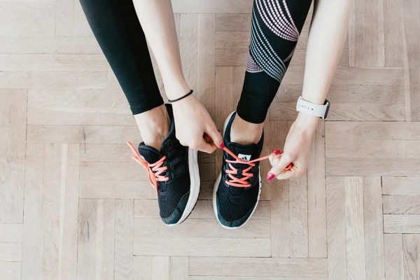 Woman tying her shoes and getting ready for a workout.