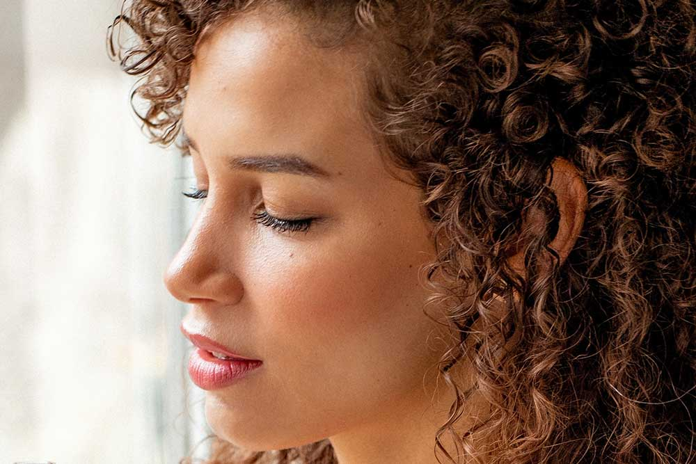 Close up of a woman with her eyes closed, curly hair, and make up on..