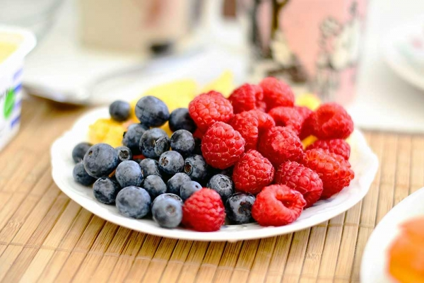 A plate of raspberries and blueberries on a wooden table.
