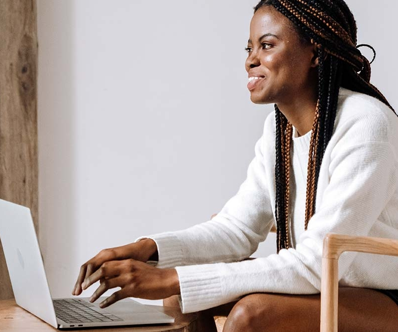Woman sitting down and smiling while on a MAC laptop.
