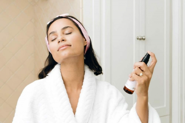 Woman in a robe spraying her face with a refreshing mist.