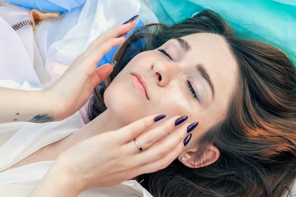 Woman laying down with her hands close to her face.
