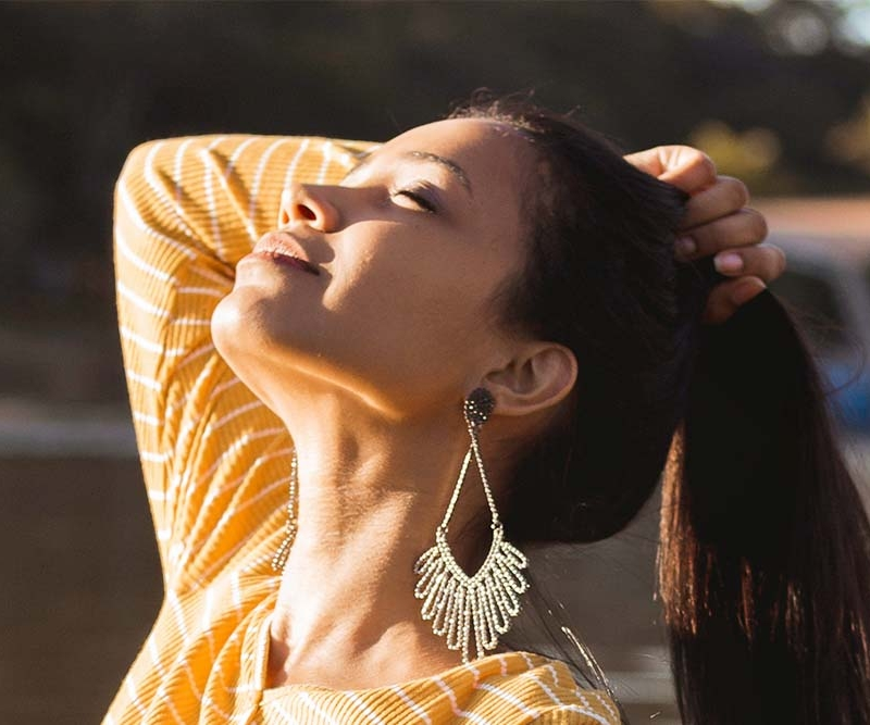 Woman grabbing her hair while looking into the sunny sky with her eyes closed.