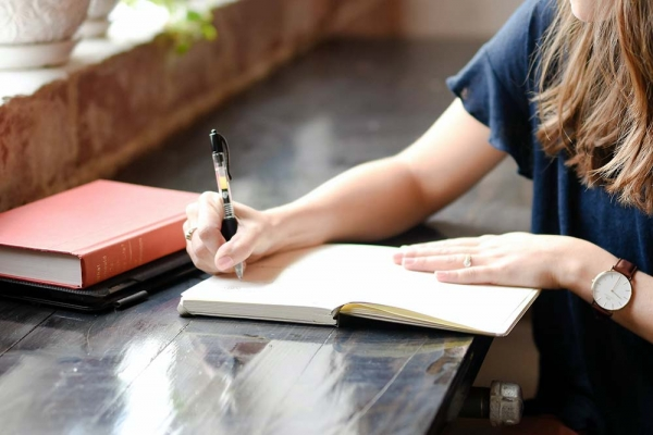 Woman seated at a table writing in a journal - practice gratitude daily in any form including keeping a journal.