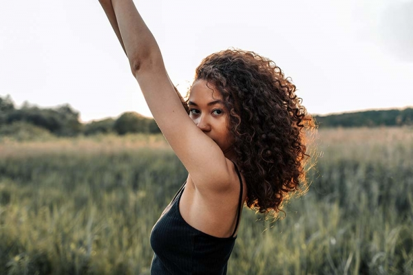 Woman with her hands up in the air outside in a grass field looking into camera - grab some fresh air to help cope with depression.