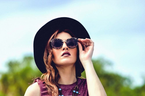 Woman with makeup looking at the sky with sunglasses and a hat.