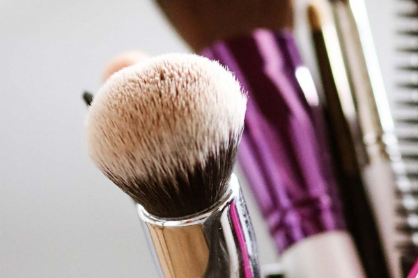 Zoom in of a powder brush in a container with other brushes.