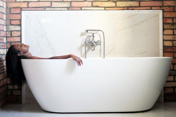 Woman laying back in a bath tub.