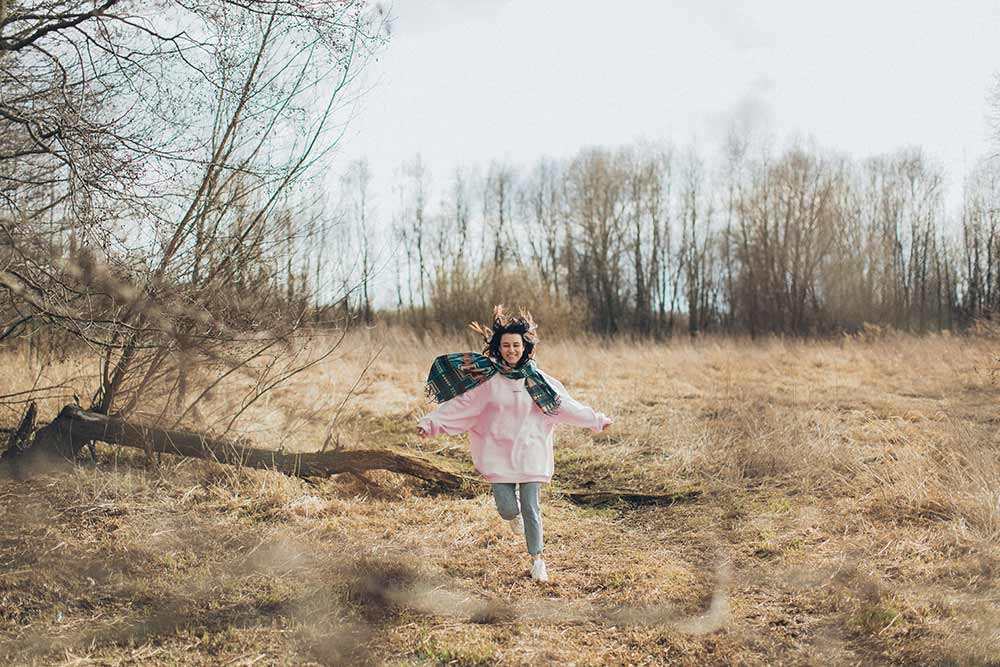 Woman running through a forest area during cold fall weather