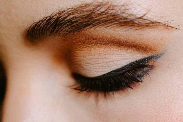 Close up of an eye with black and orange eyeliner.
