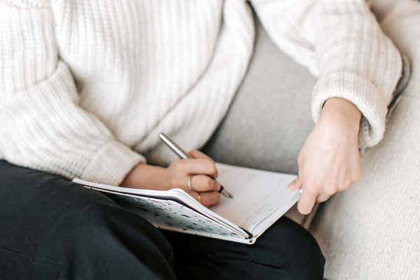 Woman writing into a journal while on seated on a couch.