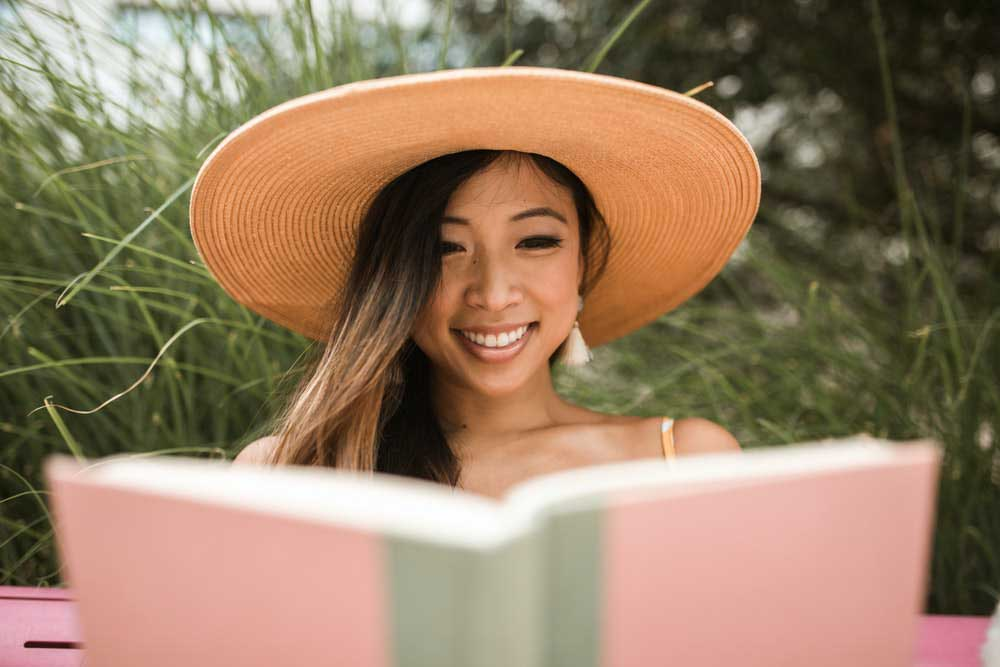 Woman wearing a hat while reading a book outside.