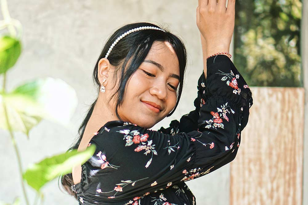 Woman smiling with her arms up in a dancing pose.