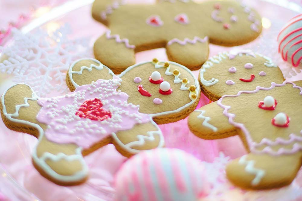 Gingerbread cookies, decorated in pink frosting, on a pink plate.