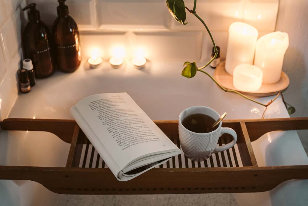 In the tub, with a book, cup of tea, dimmed lights, and candles lit.