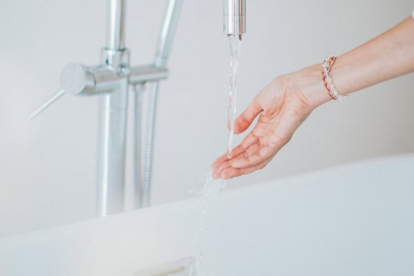 A person running bath water into their hand.