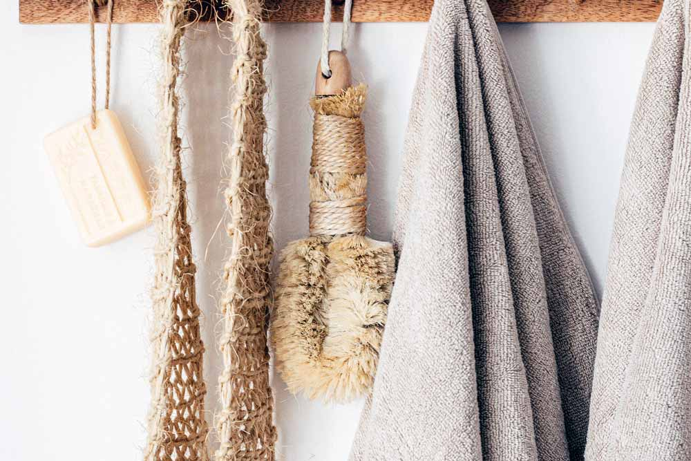 A loofah, a pair of towels, and soap bar on a hanger.