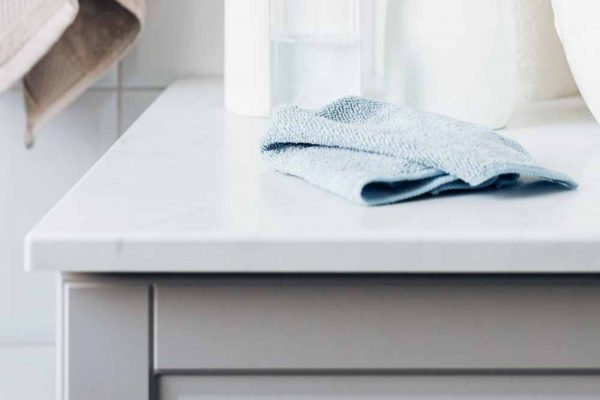 A blue wash cloth sits on the counter in a bathroom.