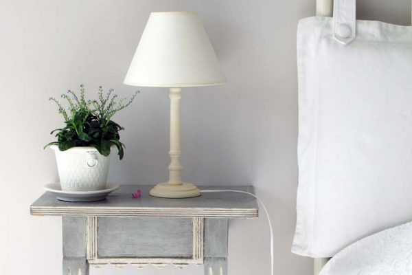 Nightstand next to bed with a lamp and plant.