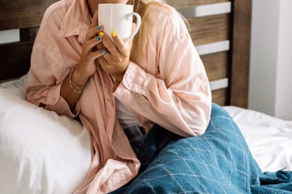 Woman enjoying a cup of coffee on her bed while snuggled in a blanket.