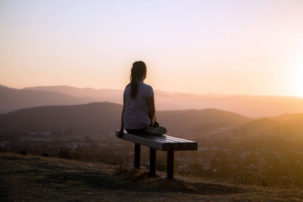 Woman sitting on a bench outside early in the morning after a quick workout.