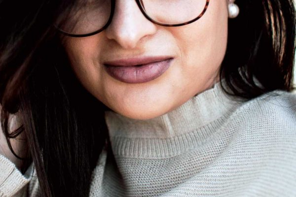 Closeup of lips - woman wearing turtleneck sweater and glasses.