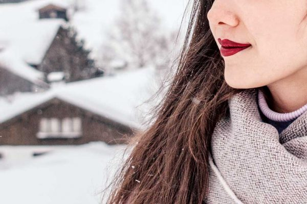 Outside in the snow with warm clothing and red lipstick.
