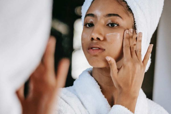 Person of color applying face lotion to their cheek.